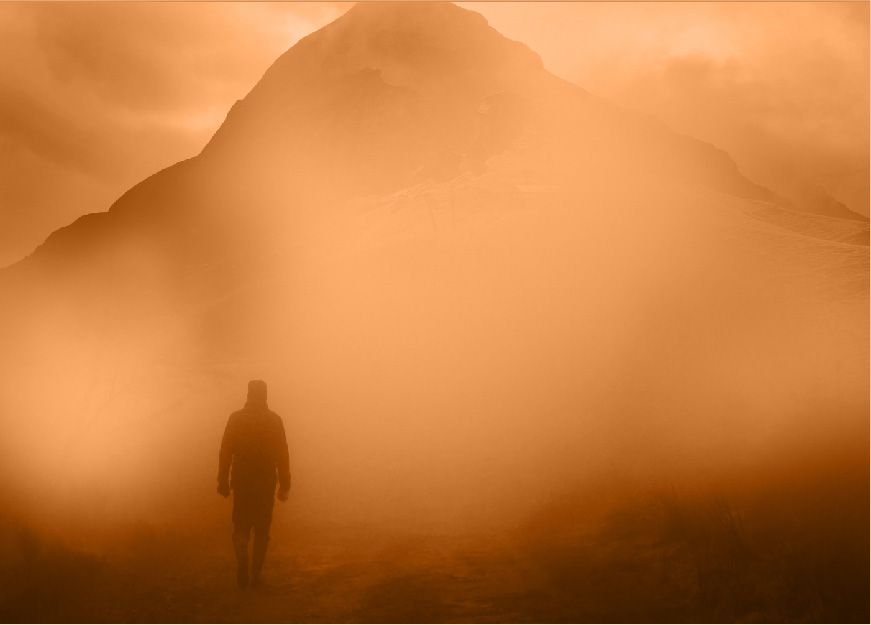 A landscape shot of a desert/mountain. The shot is foggy/sandy, and a silhouette of a person can be seen in the distance