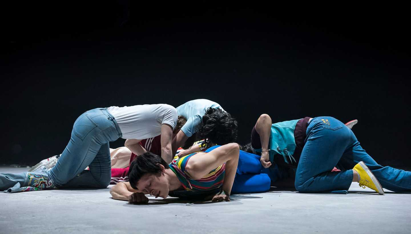 A group of dancers lie in various positions crouched and lying on the floor. They are dressed casually, in jeans and t-shirts. The background is black, the floor is concrete.